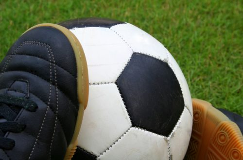 A worn-out soccer ball with a pair of futsal shoes on grass.