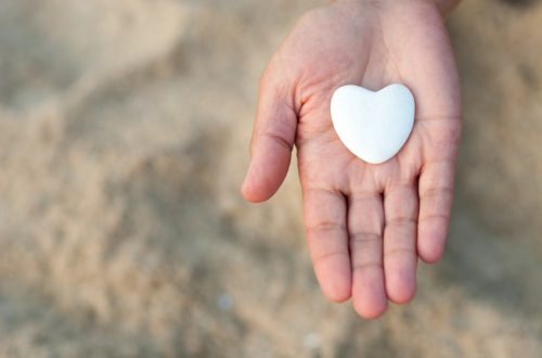 Hand holding a stone heart on the beach. Symbol of life.